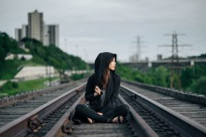 girl with japanese hair straightening sitting on railroad tracks